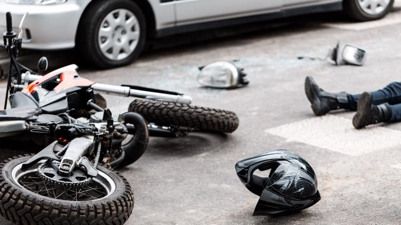 A person lying in the road after a motorcycle accident.