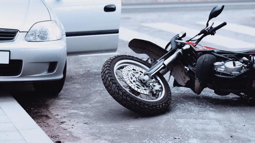 A motorcycle lying on the ground after being struck by a car.