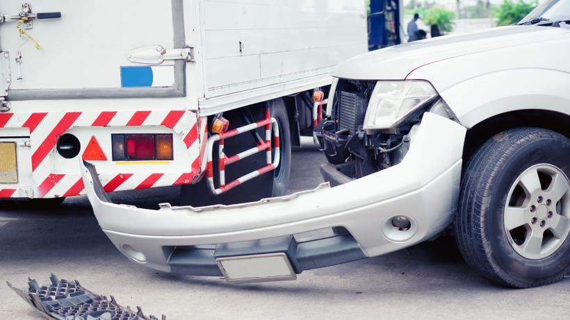 A car that had its front bumper knocked off in a truck accident.