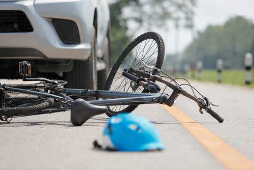A bicycle lying in the middle of the street, beside a blue helmet.