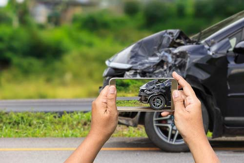 An individual taking pictures at the scene of a car accident.