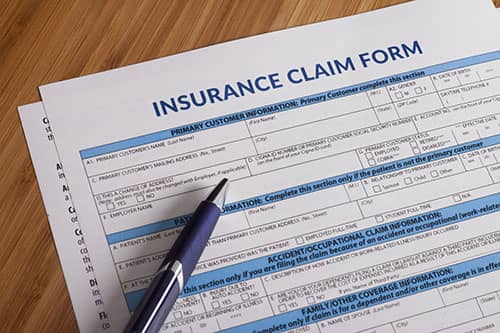 Car insurance claim form and pen and pen