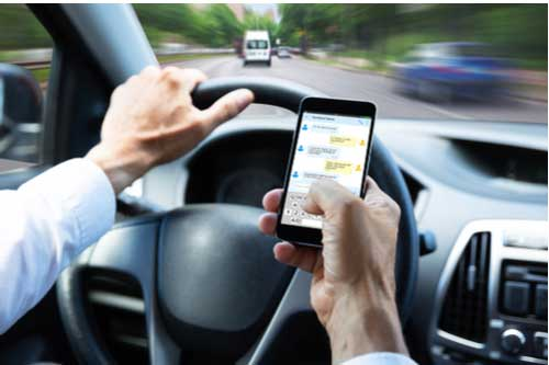 Man texting and driving, concept of Fayetteville distracted driving accident lawyer