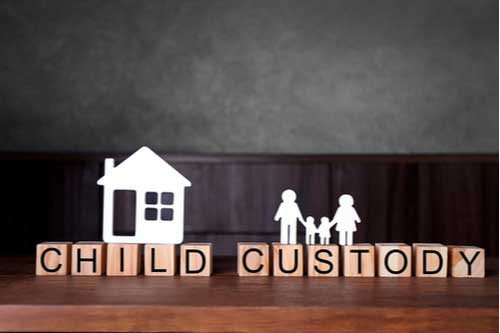 Paper house and family on blocks with words child custody, Fayetteville divorce lawyer concept