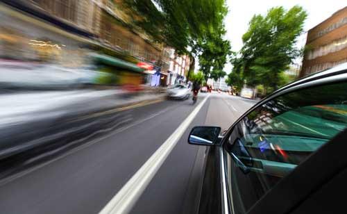 Car speeding on city street, concept of Fayetteville speeding accident lawyer